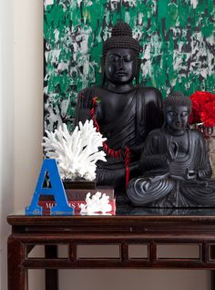 Vintage coral, textural painting, carved timber Buddhas, books and an old typographic sign
