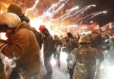 Fireworks explode near anti-government protesters during clashes with riot police at the Independence Square in Kiev, Feb. 18. Vasily Fedosenko / Reuters