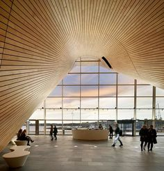 The undulating oak underbelly of four auditoriums bursts through the glazed facade of this concert hall in Kristiansand, Norway.