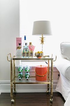 Chic living room boasts a white Ikea sofa next to a gold bamboo bar cart filled with libations doubling as an end table.