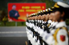 A picture of Chinese President Xi is seen behind soldiers of China's People's Liberation Army marching during a training session for a military parade to mark the 70th anniversary of the end of the World War Two, at a military base in Beijing