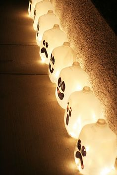 Fun and cheap halloween decorations using milk jugs-fill with sand so they don't blow away and then tye string to glow sticks for easy removal if they need replacing.