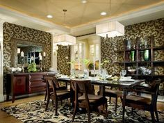 Mixtures of pattern from the glimmering scrollwork accents on the walls and the bold patterned carpet add a little drama to this clean-lined dining room with linear features.