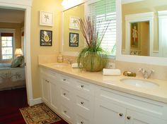 wellborn cabinets Tropical Bathroom Designs Hawaii area rug hardwood floor houseplant marble counter molding sconce shaker cabinet shaker vanity undermount sink white cabinet yellow