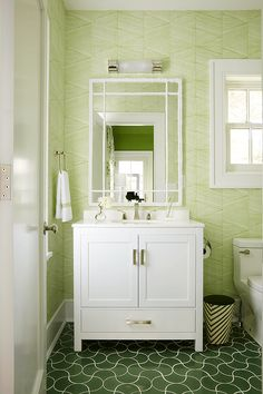 "Meg Braff Designs - Calming Meg Braff Endura Wallpaper lines the wall of this gorgeous white and green bathroom fitted with green wavy floor tiles framing a white bath vanity adorning polished nickel hardware and positioned underneath a white faux bois mirror lit by an Oxford 18"" Bath Sconce."