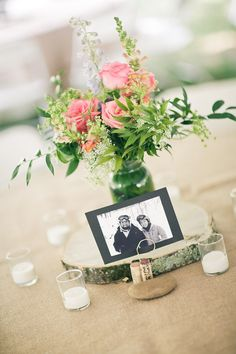 table arrangement: flowers in mason jar, set on wood slab, surrounded by votives. photo.