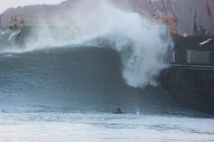 Surfer takes advantage of the giant waves along side Newlyn Pier, Cornwall