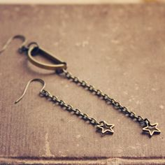 moonchild. a pair of golden assymetrical moon and star earrings. @Naomi Gottlieb-Miller