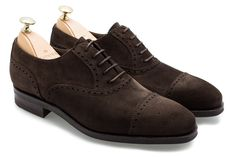 The 10051 brogued oxford by Carmina sits on the soft, square Rain last. Featuring broguing and a toe cap, all in a rich brown suede, the dainite sole gives this shoe the casual sophistication that it needs.