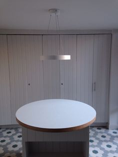 Ceiling light fitted over round island unit with 'hidden kitchen'