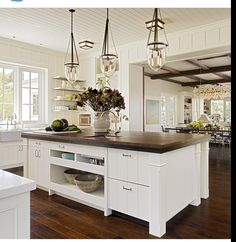 Butcher Block counter tops on Island which features lots of storage space.  LOVE the pendant light fixtures AND those gorgeous coffered ceilings in the dining area!  #KitchenIdeas #KitchenIsland #KitchenDesign