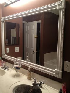 DIY bathroom mirror frame. White styrofoam molding, wood corner squares, and a craft hot glue gun. No paint. No mess. Took 30 mins! Cat included.
