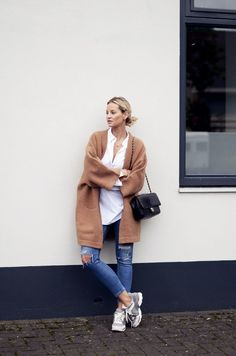 Shop this look on Lookastic: https://lookastic.com/women/looks/coat-dress-shirt-skinny-jeans-athletic-shoes-crossbody-bag/7014 — White Dress Shirt — Brown Coat — Black Quilted Leather Crossbody Bag — Blue Ripped Skinny Jeans — Grey Athletic Shoes