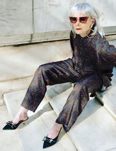 Over 50 style blogger: Lyn Slater of Accidental Icon wearing printed pyjamas with velvet kitten heels and red sunglasses