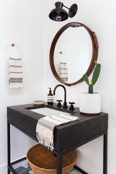 boho bathroom with black sink and round mirror