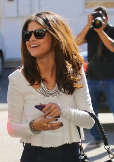 Selena Gomez looks super glam stepping out with shades and a smile! #style