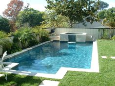 Travertine coping picture frames the pool in this landscaped environment. Soothing 3' wide sheet waterfall from the raised spa.