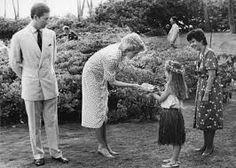 November 8, 1985: Prince Charles & Princess Diana on the grounds of the Kahala Hilton Hotel as a hula girl presents Princess Diana with t-shirts for Prince William & Prince Harry.