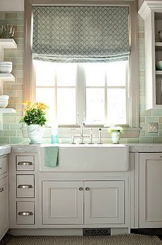 love the farmhouse sink, soft roman shade, aqua glass subway tile backsplash, open shelving, white cabinetry