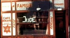 """Vienna, 1938: The coming of the Nazis had an immediate impact on the local Jews. Here is a Jewish grocery shop defaced by Nazi thugs. Black paint has been splashed on the shop sign, the word """"Jew"""" has been painted on the window, and the Star of David has been painted on the shop's poster. People daring to continue shopping in Jewish shops run the risk of accosting """"spontaneous punishment"""" in the hands of local stormtroopers."""