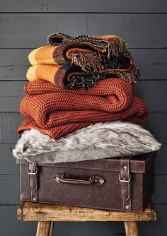 Channel ski-lodge chic with chunky-knit cushions and throws. Burnt orange shades matched with mustard, navy and yellow creates an earthy, warm feel. #chic_autumn_decor