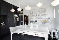 Love this eclectic kitchen and its creative use of black and white.  The placement of the sink, in the middle of the kitchen with a free floating table/counter, is dramatic  and calls for people to gather around.
