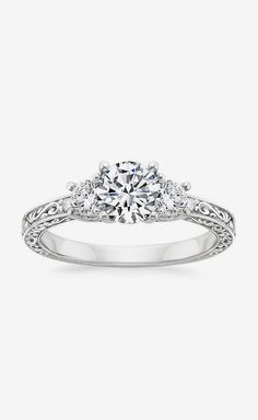 Three Stone Ring Filigree. I love the two stones flanking the center stone. It's balanced and I love that. The band is intricate, reminds me of Irish script and scroll. -KB