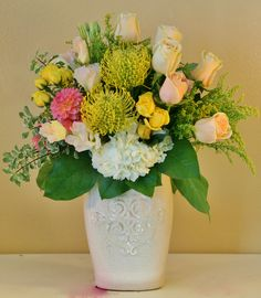 pastel flowers including pin cushion protea peach roses yellow mini roses hydrangea and more in a decorative ceramic vase. #Riversideflowers #Flowersriversideca #Riversidecaflowers #Flowers #Florist
