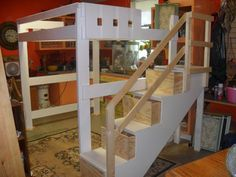Queen size loft bed with staircase and drawers painted white.
