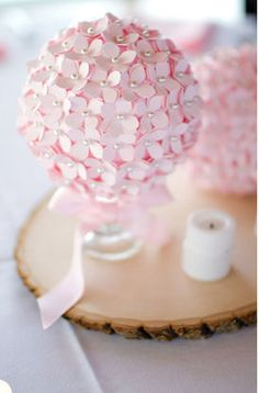 Unique centerpiece idea: a styrofoam ball covered in paper flowers with pins stuck through the center. Should sit nicely on a candleholder or margarita glass.