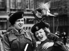 Lutz Dille :: Two uniformed women stand with London pigeons landing on the head and arms of one of them, possibly in Trafalgar Square, London, ca. 1961 /  more [+] by this photographer