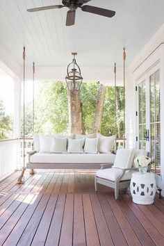 Gorgeous cottage porch features a gray wash porch swing sofa hanging by ropes from a white beadboard ceiling and topped with a light gray cushion and white border gray white border pillows accented by a matching accent chair sat beside a white rope stool lit by a antiqued brass lantern hanging over a composite porch board floor.