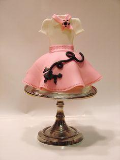 Un pastelito con forma de vestido y decorado con un perrito.