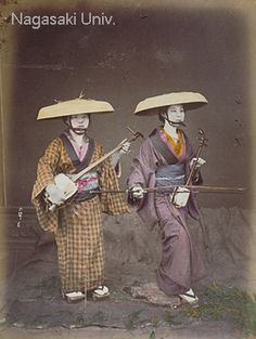 Two women play an instrument while they tell a story. The woman to the left holds a shamisen, and the woman to the right holds a Kokyu. The kokyu is a string instrument some what smaller compared to the shamisen, and is often used for ensembles with the shamisen and koto. about 1870's by photographer Suzuki,Shin-ichi