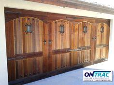 Custom wood garage door with arch top design. Enhanced with decorative clavos, speak easy grills, handles and hinges.