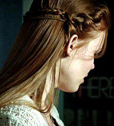lydia martin hairstyle: run a straightener through it to give it that sleek, shiny look. Part in middle and comb the rest back. With both sides of the bangs, twist them toward the center of your head and then began braiding. Leave out a strand or two to fall in your forehead. Add hair into the braid as you go Make sure to not braid below the ear, instead staying about an inch higher. Braid both sides of the bangs like this create the tinier braid underneath the larger one,