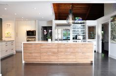 modern kitchen remodel with high wooden ceilings, custom lighting, white cabinets, dark tile flooring, modern art pieces, and stainless steel appliances... by the BEST custom construction company in central Florida | www.allinconstruction.com