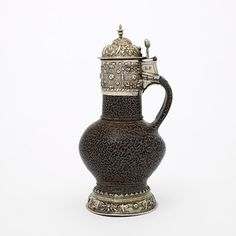 The mottled brown glaze on this jug was known in England as 'tigerware'. Glazed stoneware such as this was imported in large quantities from the German Rhineland in the 16th century and often mounted in precious metal. Inexpensive objects of turned wood and stoneware, and more costly glass vessels were often transformed by adding decorated mounts of silver, pewter and gold.