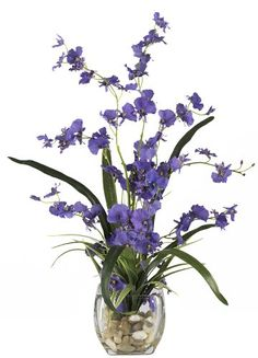 Silk floral arrangement in a glass vase.Product: Faux floral arrangement Construction Material: Silk and glass Color: Purple Features: Filled with curvy stalks of dancing lady orchid blooms Accented with river rocks and lush leaves Dimensions: H x W x D Artificial Floral Arrangements, Silk Floral Arrangements, Artificial Plants, Halloween Floral Arrangements, Vase Arrangements, Silk Orchids, Purple Orchids, Purple Lilac, Faux Flowers