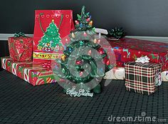 Christmas presents on the table behind a small, lighted, ceramic tree.