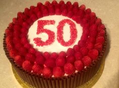 A 50th birthday cake for a friend's husband. Joconde sponge brushed with amaretto, raspberry butter cream, fresh raspberries and dark chocolate cigarellos. Www.bakingfanatic.wordpress.com