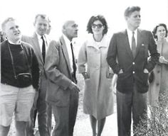 """""""except for caroline kennedy and sally fay, the primary members of the kennedy party are present in this picture. from left to right are paul fay III, paul fay jr., colonel sheads, mrs. kennedy, president kennedy, and anita fay. they are looking at the front (east side) of the north carolina monument. """""""