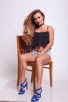 Beautiful woman sitting on a chair in shorts jeans  stock photo (c) DCStudio (#8527601) | Stockfresh