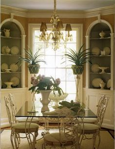 love the idea of a fern/plant stand on either side of a window in the dining area.