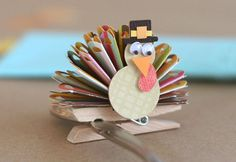 Thanksgiving Turkey Place Card by Sweet Designs. To make a the feathers, cut a strip of double-sided cardstock and use your favorite paper edge puncher on one of the long edges. Use a scoring-board to score lines and accordion fold it up! Adhere to a clothespin and add on your turkey body with your guest's name.  Find double-sided cardstock for this project at www.cardstockshop.com.