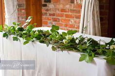 wedding ceremony table enhanced with green foliage garland. green wedding. Woodland theme wedding. @joannamarriott