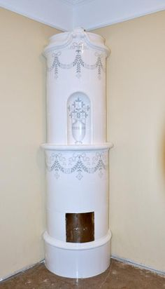Round Fireplace with shelf and niche with painted decorations. It is about 260 cm high and made ​​around 1900.