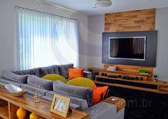 Um aparador com nichos faz a divisão entre o estar e o home-theater, que conta com um charmoso lambri em madeira de demolição como moldura para a TV de tela plana.
