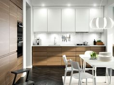 Kuchnia z drzwiami imitującymi orzech, drzwiami w kontrastujących kolorach i białym blatem. Całość uzupełniono wyciągiem ze stali nierdzewnej oraz ciemnoszarym piekarnikiem i kuchenką mikrofalową.