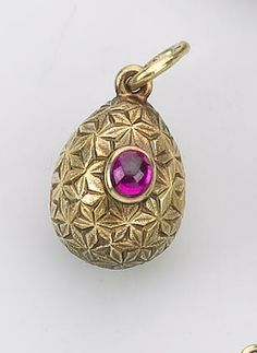A miniature Easter egg pendant, Friedrich Koechli, St. Petersburg, circa 1900. The gold body densely chased with geometric floral motifs set with pink cabochon stone, suspended from gold loop.